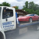 squires services towing a sports car on flatbed truck