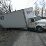 squires services truck winching a box truck out of a ditch