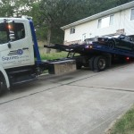 squires services tow truck towing a car from a driveway